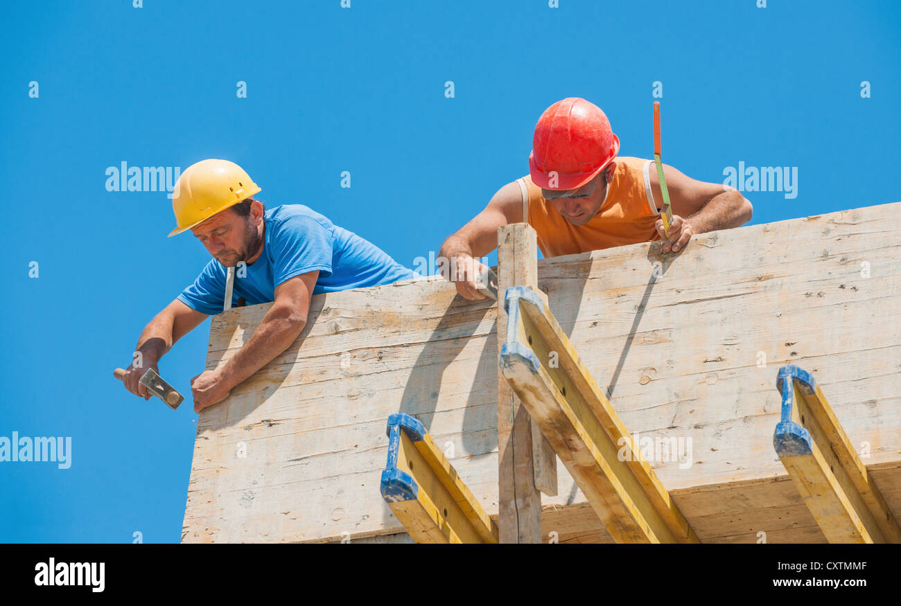Construction workers nailing cement formwork in place - Stock Image