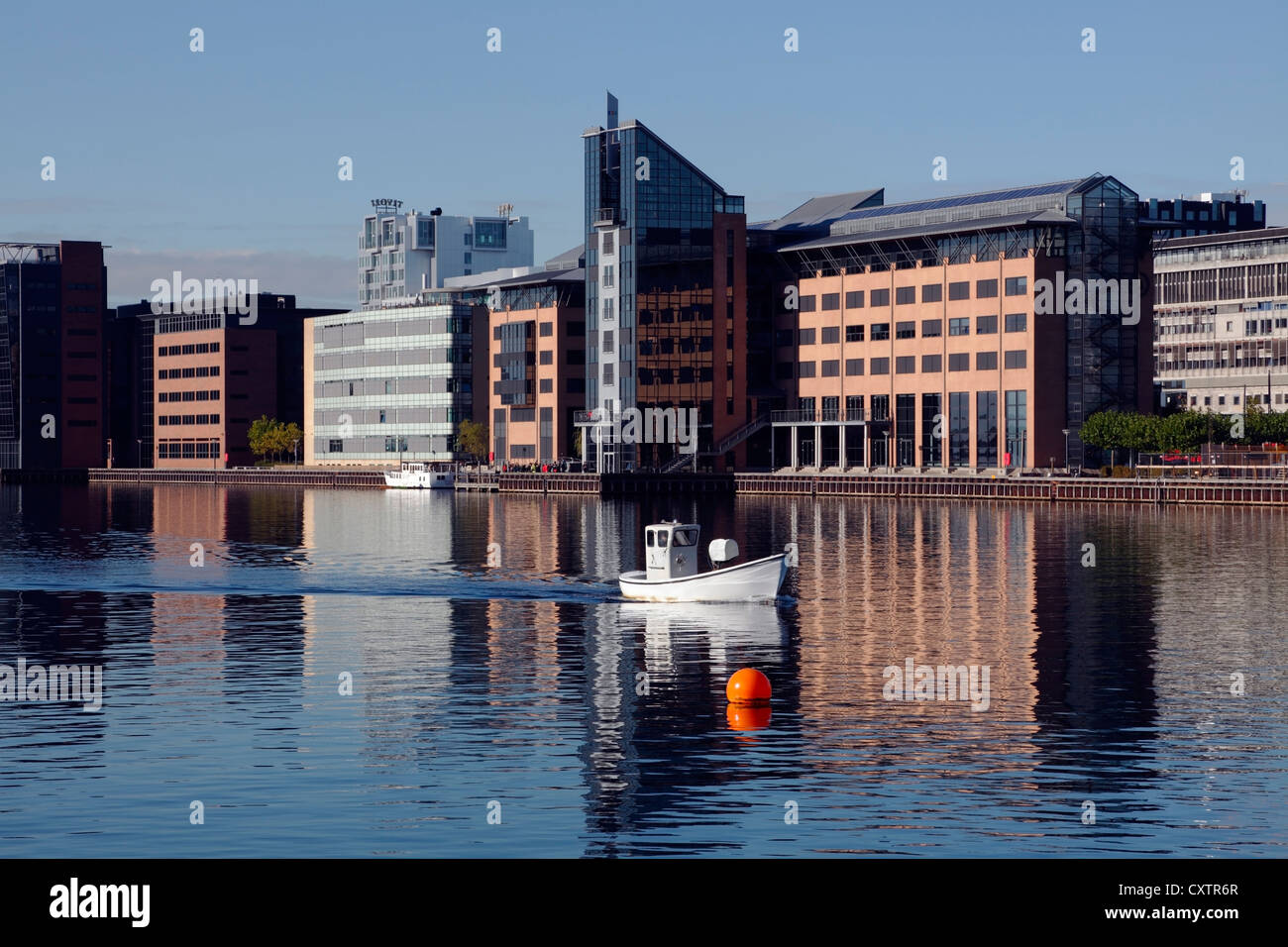 Fishing vessel in Sydhavnen (South Harbour) in the port of Copenhagen. Reflections of buildings in the water. City - Stock Image