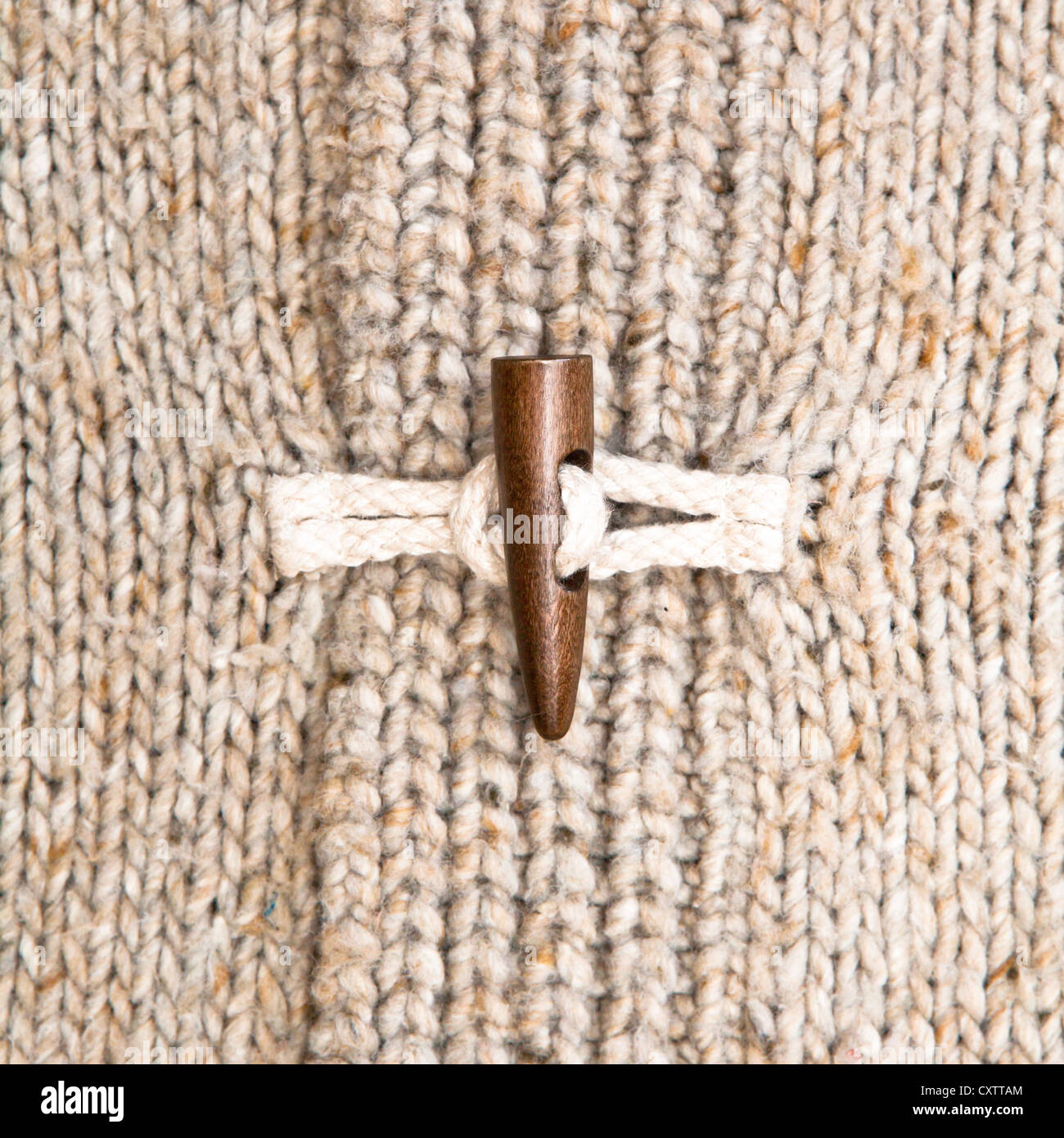 Close up of the toggle on a warm winter jumper - Stock Image