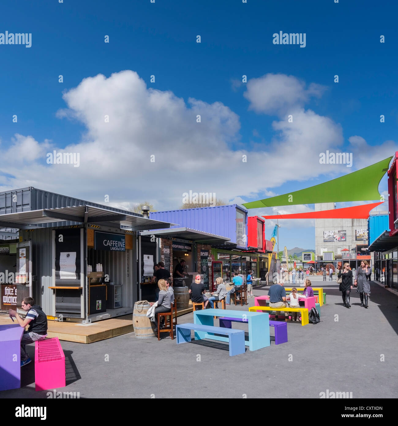 People relaxing at an outdoor coffee shop in the Container Mall, Christchurch, New Zealand. - Stock Image