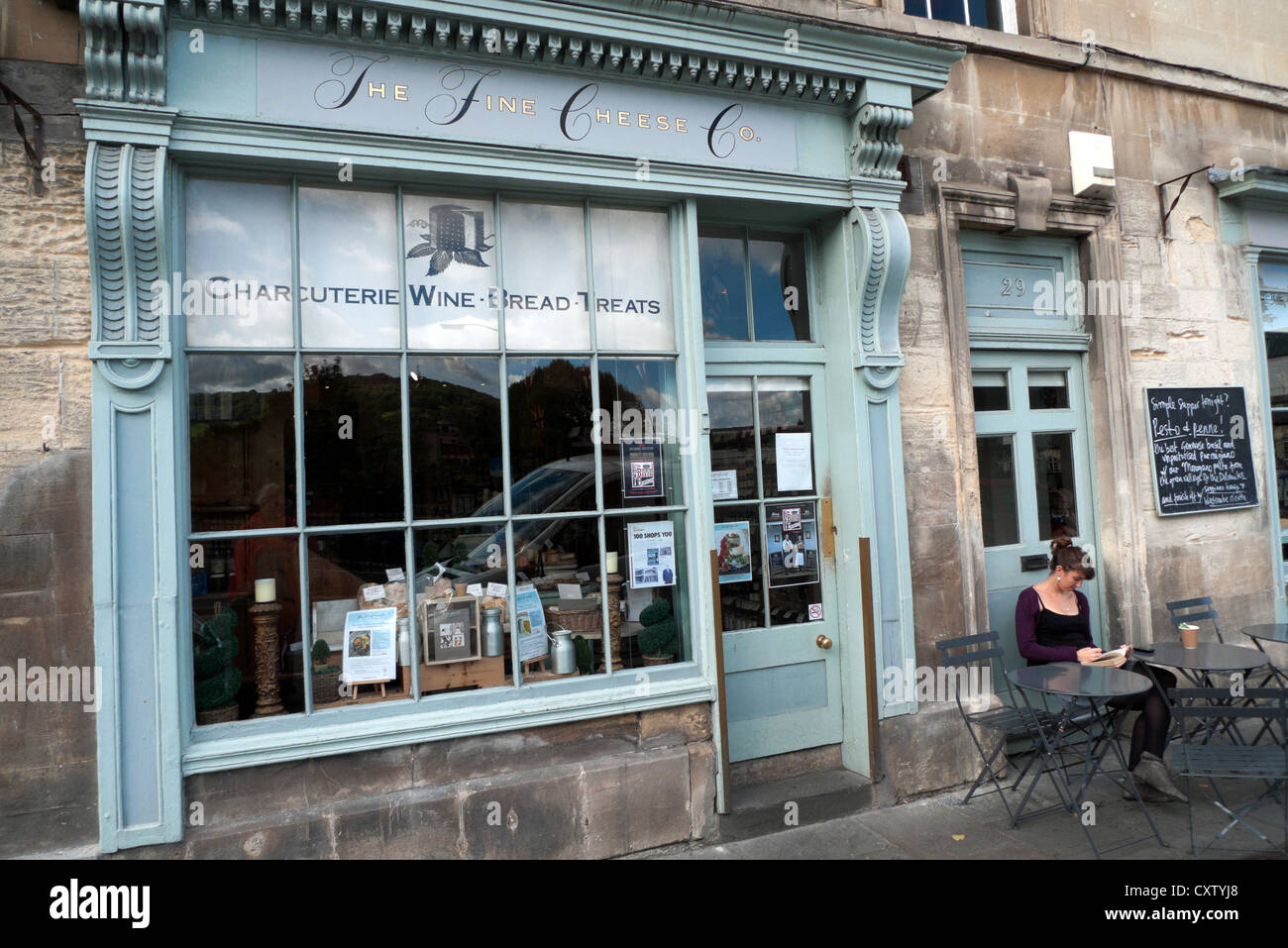 A woman sitting outside the Fine Cheese Company on Walcot Street in the City of Bath, Avon, Somerset, England KATHY - Stock Image