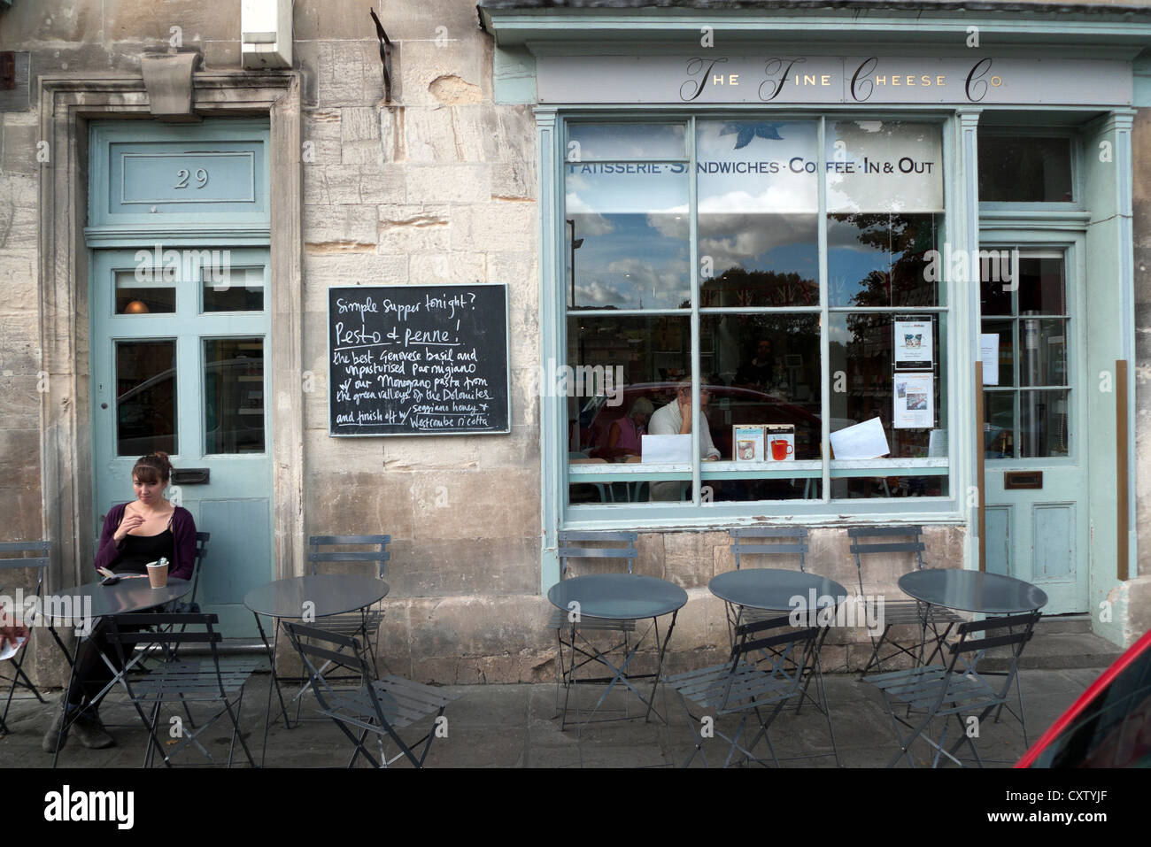 A woman sitting outside the Fine Cheese Company on Walcot Street in the City of Bath Spa, Avon, Somerset, England, - Stock Image