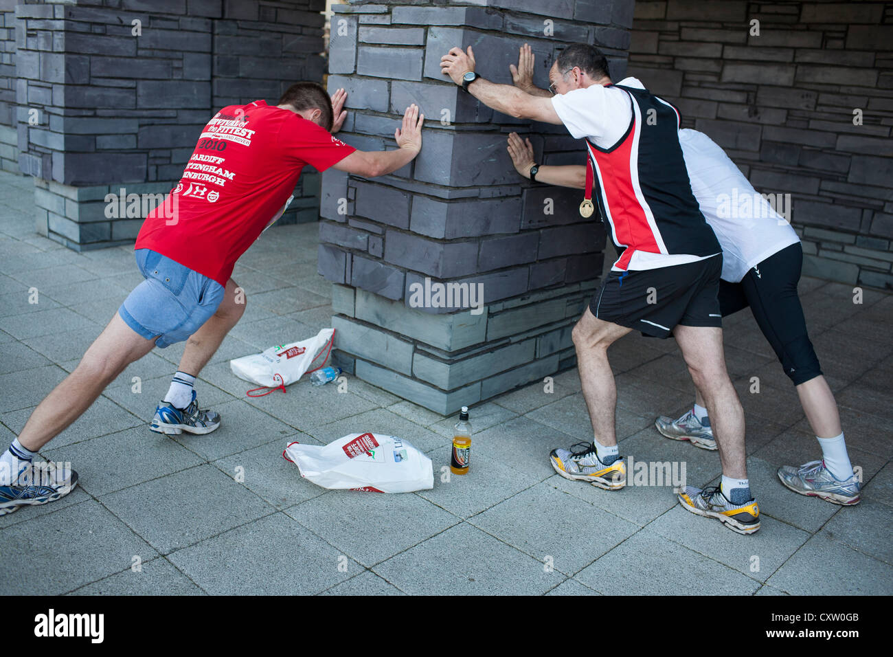 Runners stretch after taking part in the Cardiff Half Marathon - Stock Image