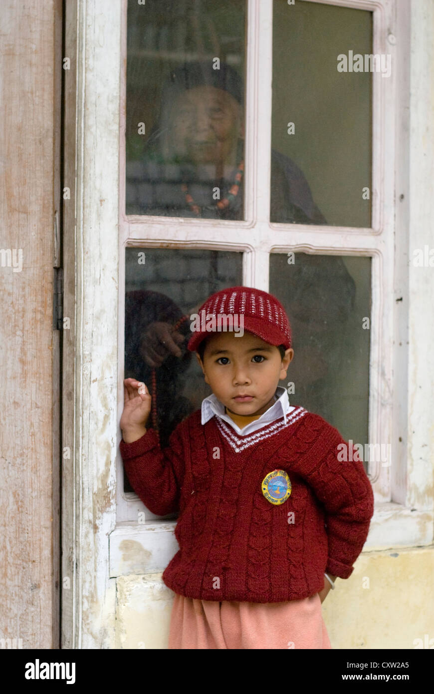 A young boy poses for the camera, while his grandmother looks on. Keylong, Northern India - Stock Image