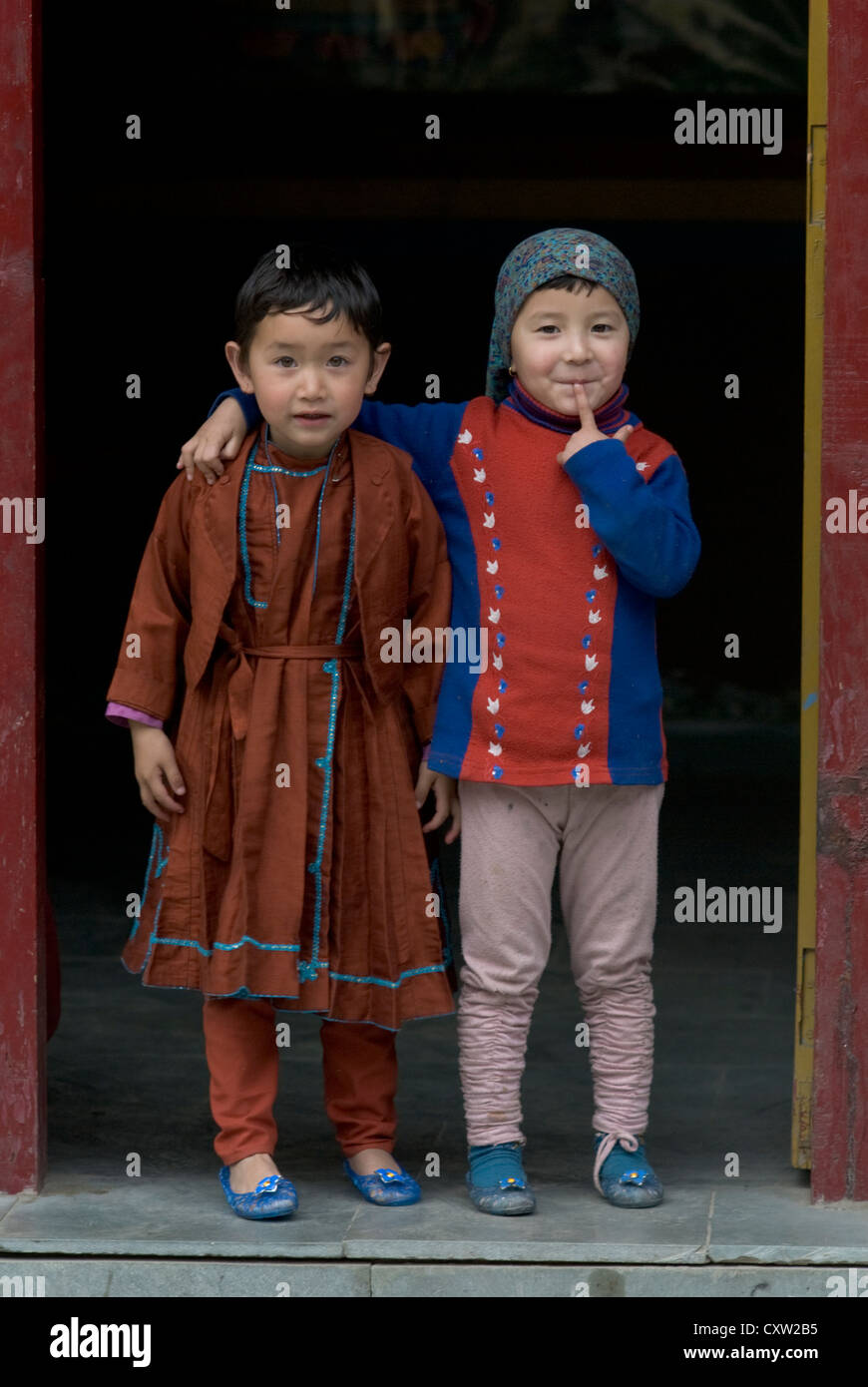 Two friends stand in the doorway of a shrine in the Himalayan town of Keylong, India - Stock Image