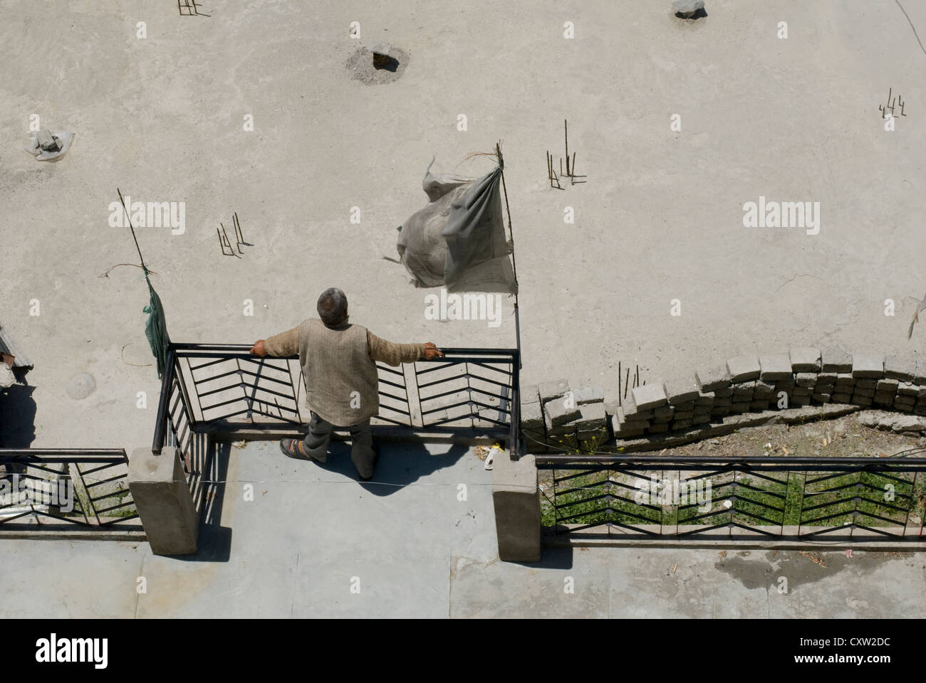 An elderly man stand on his balcony in the Himalayan town of Keylong, India - Stock Image