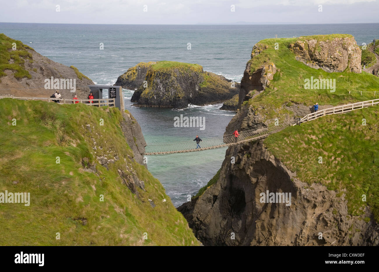 Ballintoy Co Antrim Northern Ireland Visitors crossing the popular Carrick-a-Rede rope bridge to the island - Stock Image
