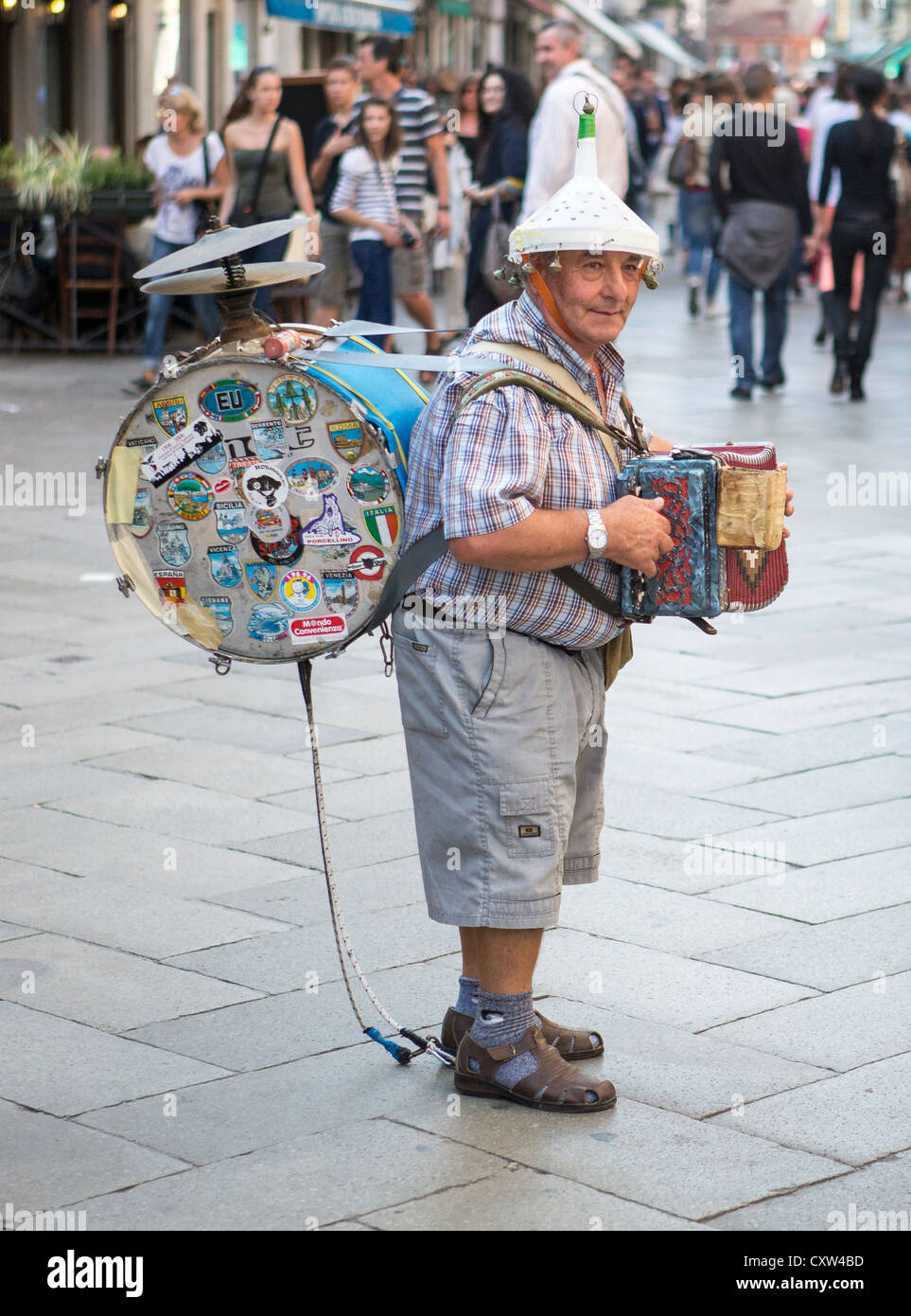 A one man band playing a concertina or small accordion,cymbals, bass drum and with a funnel with bells on his head. - Stock Image