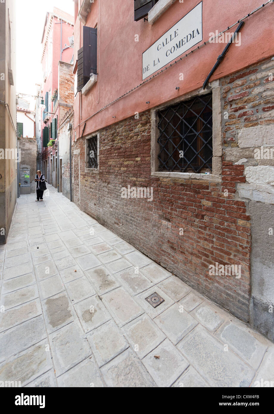 Wideangle view of the Calle de la Comedia in Venice with a woman in the background reading a pamphlet, leaflet or - Stock Image