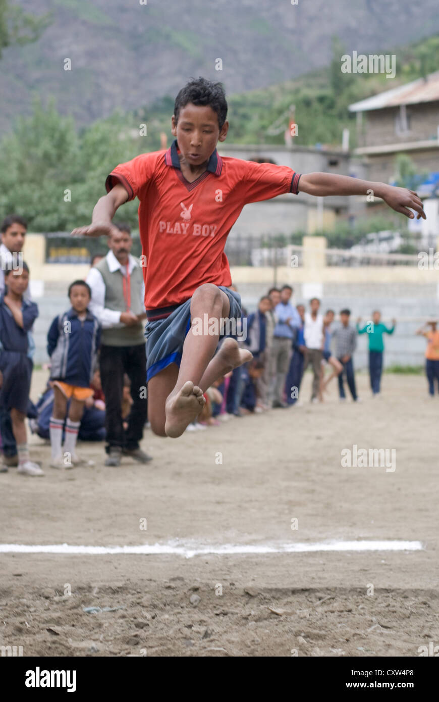A competitor in the Long jump at a schools' sports event in Keylong, North India - Stock Image
