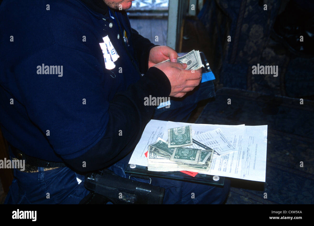 Detroit police Narcotics officer counts a pile of money seized during a drugs search warrant, Detroit, Michigan, - Stock Image