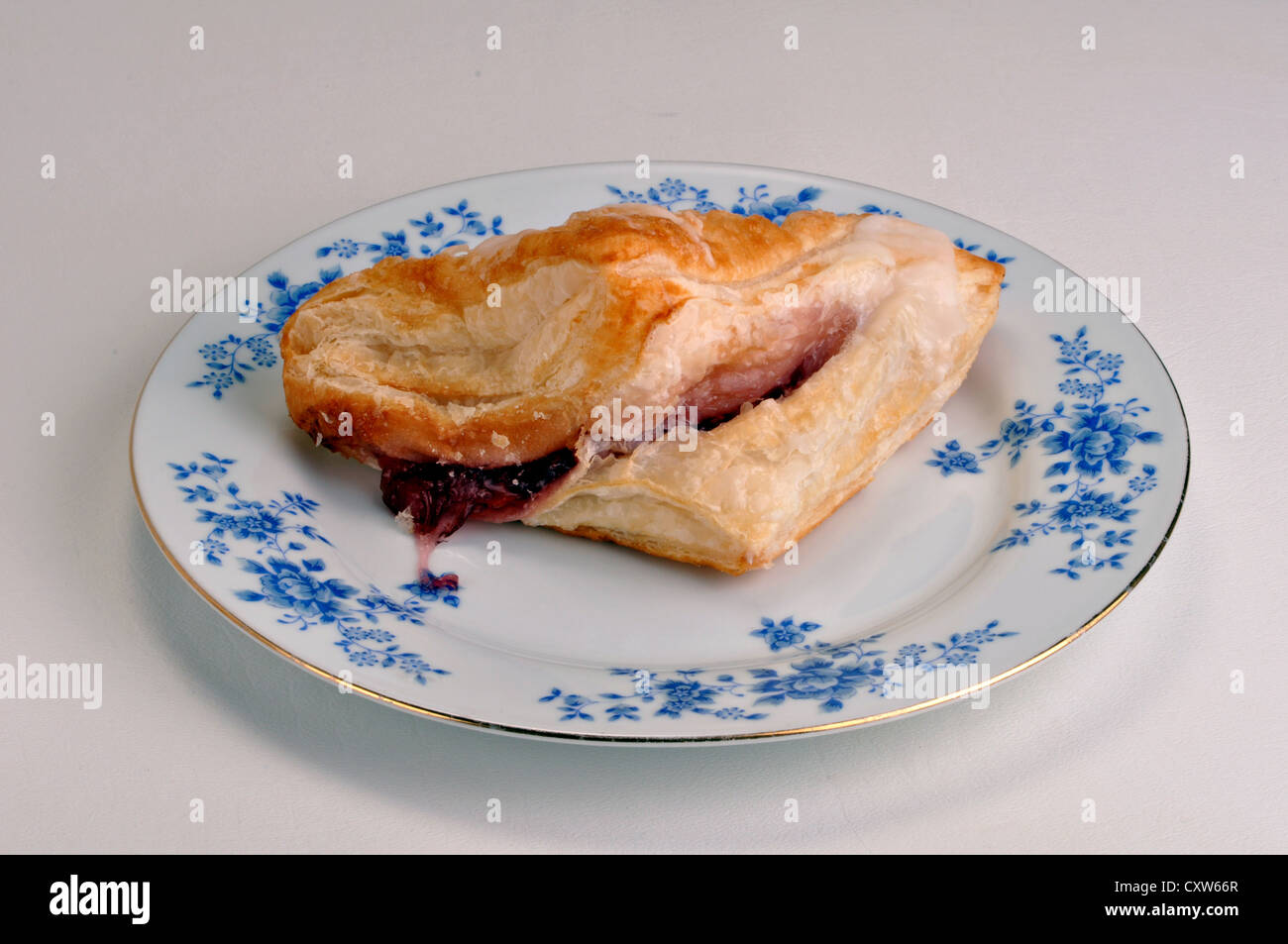 Cherry turnover on a saucer on a white background. - Stock Image