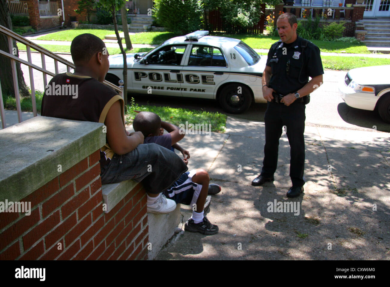 Cop in Grosse Pointe Park talking to youths, Michigan, USA - Stock Image