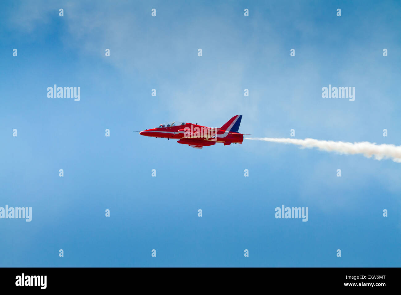 Red Arrows plane with smoke against blue sky, WESTON-SUPER-MARE, SOMERSET-JULY 23RD 2012: Stock Photo