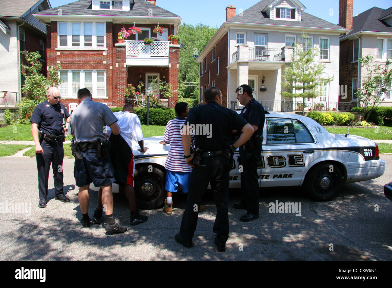 Cops from Grosse Pointe Park police department detain and search two youths, Michigan, USA - Stock Image