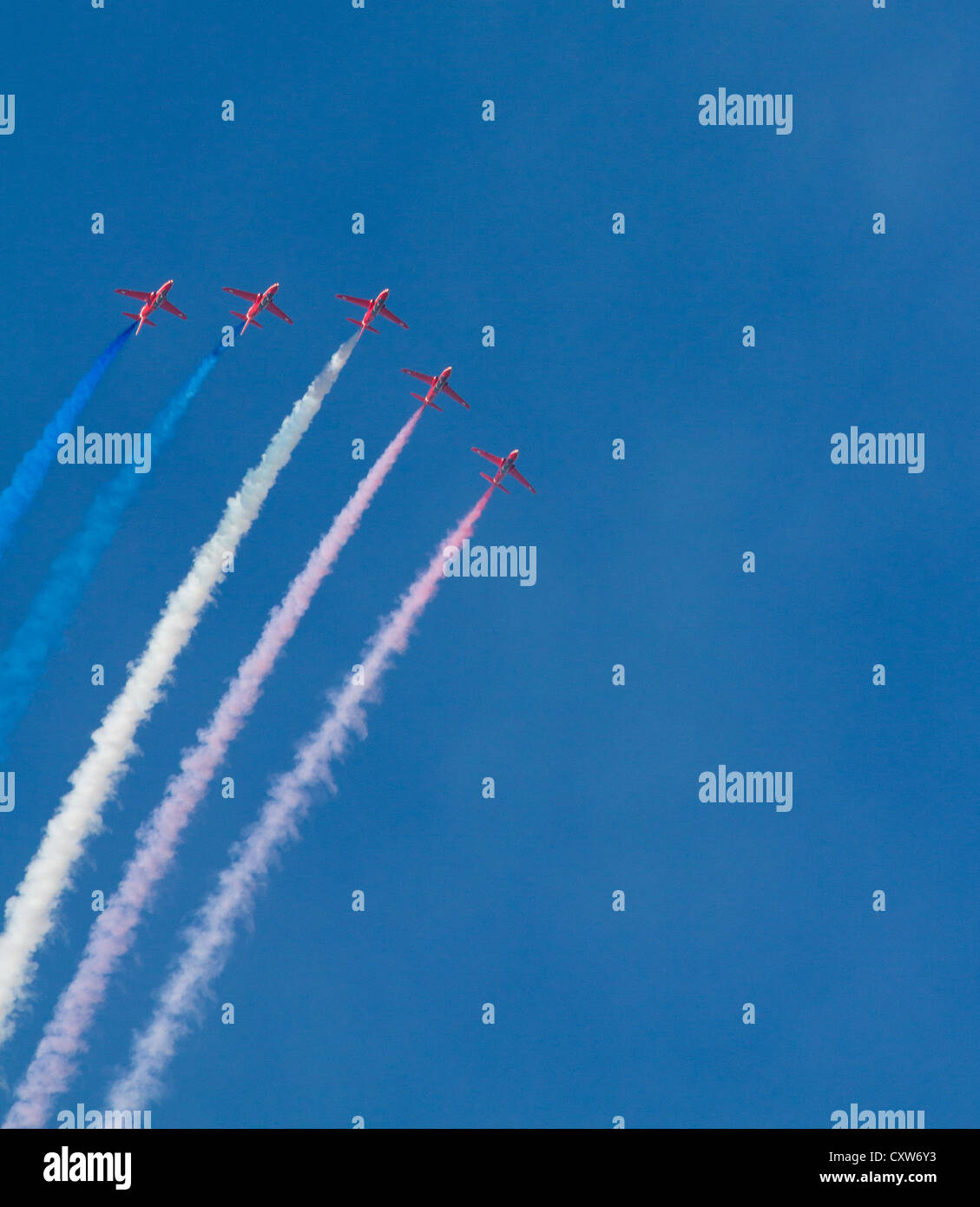 Red Arrows jets pink white blue smoke against vibrant blue sky Stock Photo