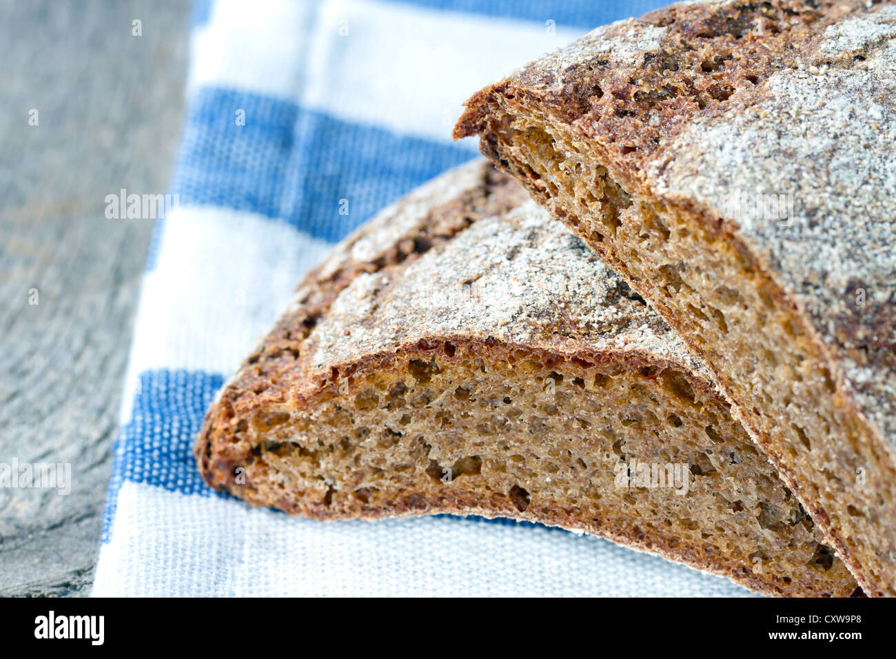Organic dark wholegrain rye bread, a new superfood, closeup on rustic wooden background and white and blue striped - Stock Image