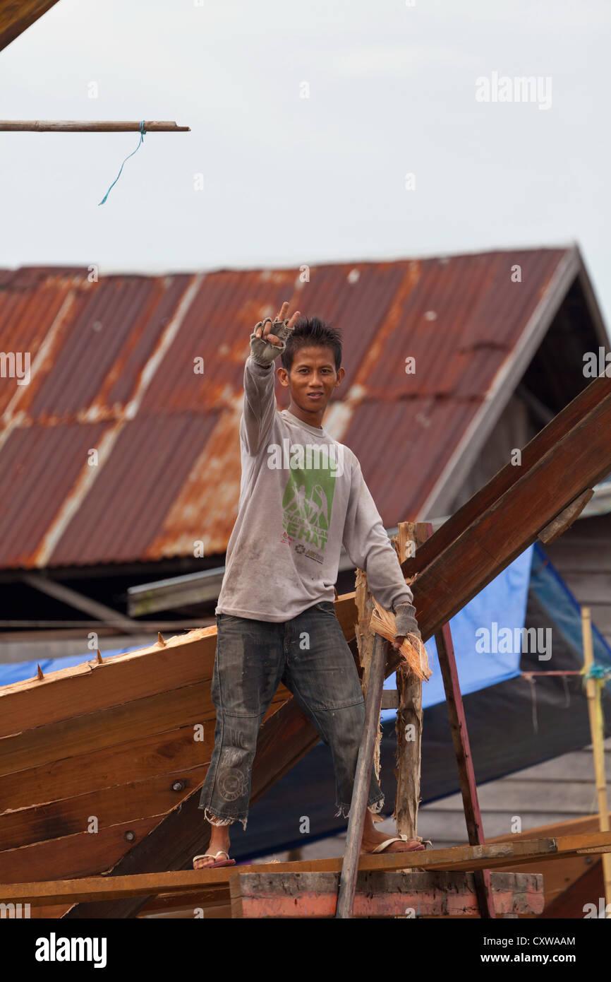 Boat Builder on a traditional Shipyard for River Boats in Banjarmasin,  Kalimantan, Indonesia -
