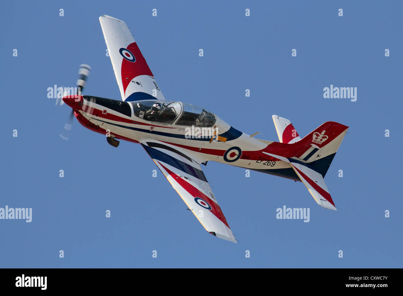 Royal Air Force Tucano T1 turboprop trainer aeroplane flying in special display colours against a blue sky - Stock Image