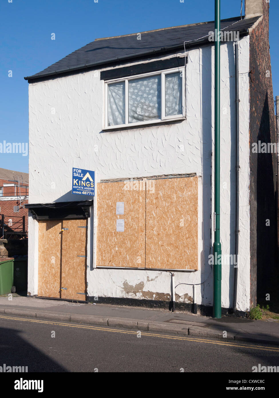 A small back street cottage or shop for sale with ground floor door and window boarded up to prevent damage or intrusion - Stock Image