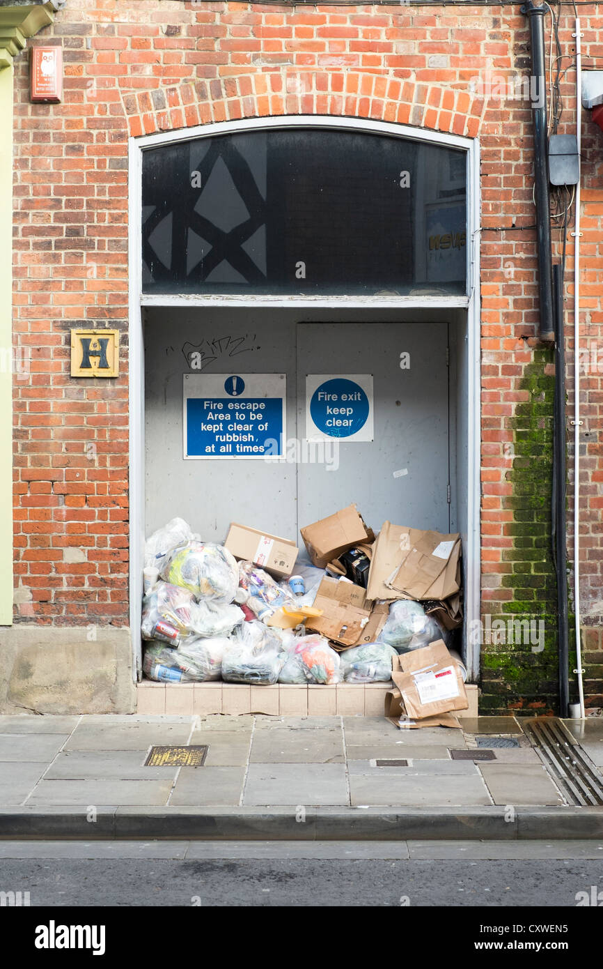 Bags of rubbish blocking a fire safety exit door - Stock Image