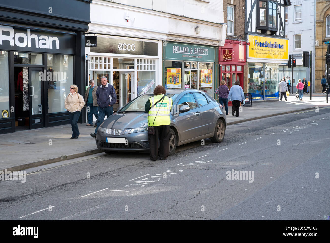 UK Traffic Warden or Parking Ambassador putting a parking ticket on an illegally parked car in the street - Stock Image
