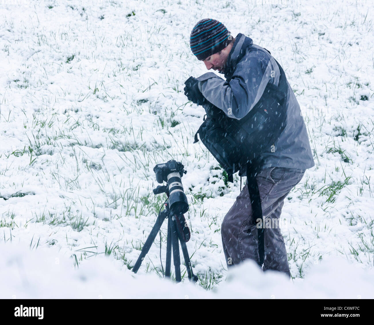 A photographer mounting his camera on a tripod to capture a recent snow fall - Stock Image