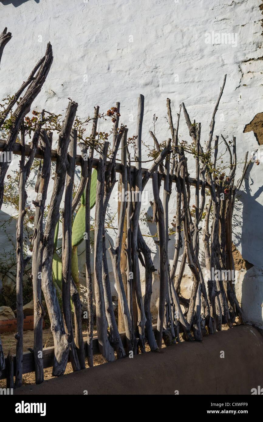 View of a primitive wooden fence constructed of tree branches at the El Presidio de Santa Barbara, Santa Barbara, - Stock Image