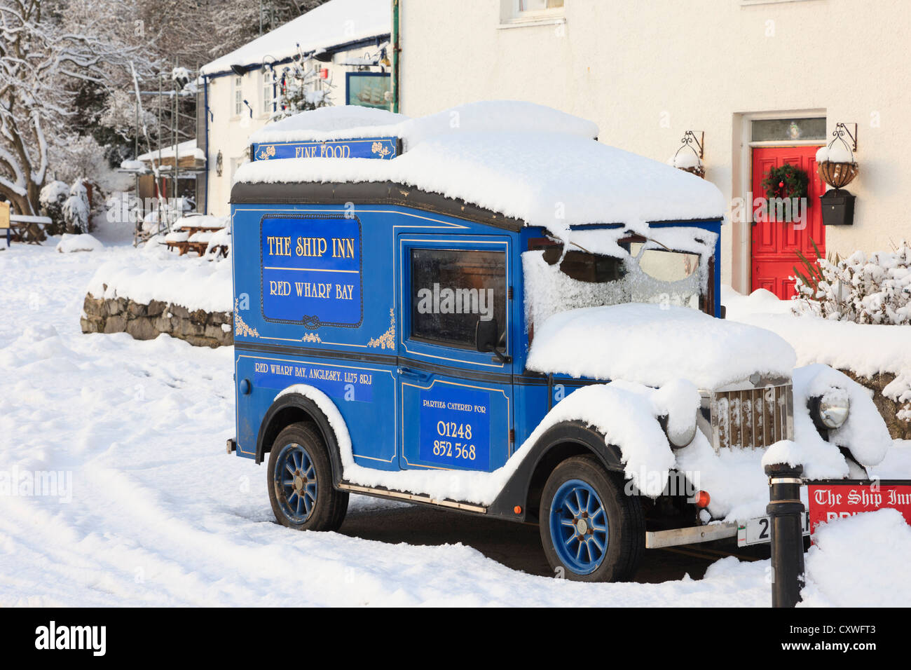 Vintage car advertising the Ship Inn village pub in winter snow in Red Wharf Bay, Isle of Anglesey, North Wales, - Stock Image