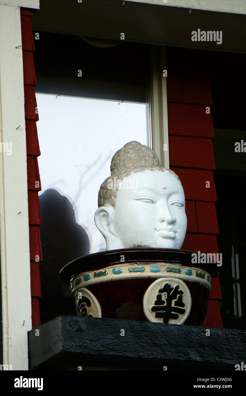 Buddha head statue on a windowsill - Stock Image