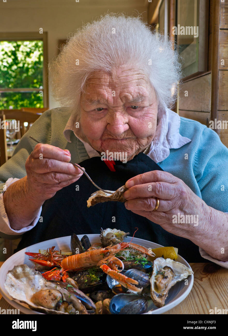 Happy elderly 99 year old lady enjoying a luxury shell fish meal in large dining room facility - Stock Image