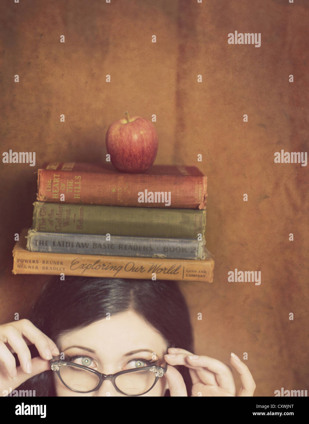 Partial face of a young woman wearing vintage glasses and blancing four books and an apple on her head - Stock Image