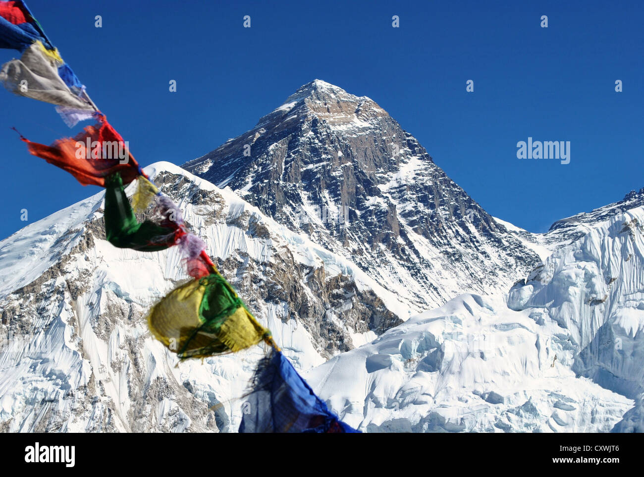 View of Mount Everest with blue sky backdrop and Buddhist prayer flags in foreground - Stock Image
