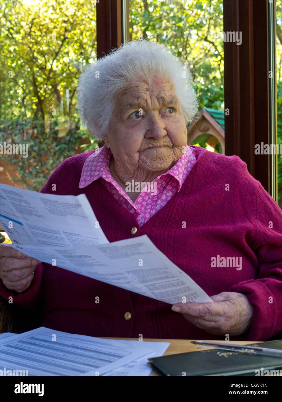 Concerned elderly senior lady at home reading and  contemplating her latest financial statements and bills - Stock Image