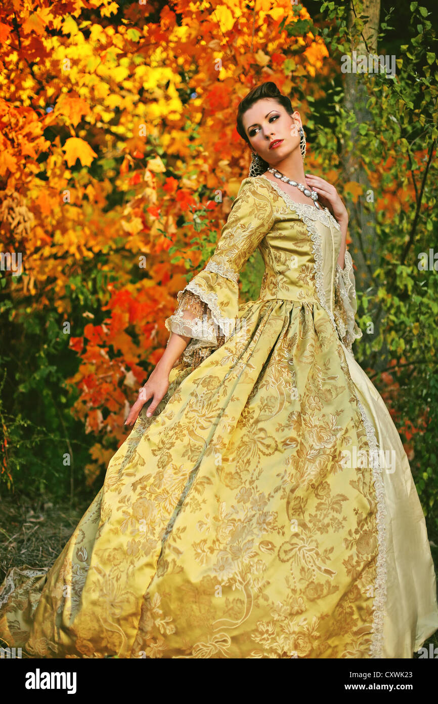 A pretty young woman in her late teens or early 20s in a beautiful fancy dress with colorful autumn trees - Stock Image