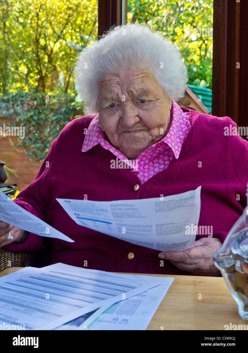 Concerned elderly senior 99 years lady at home reading her latest financial, energy, heating household bills,investments - Stock Image