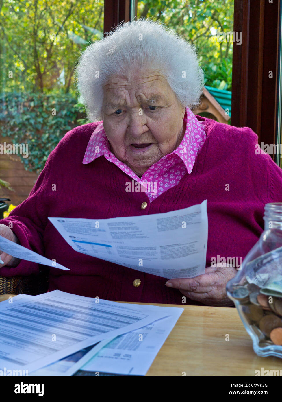 Concerned elderly senior 99 year old lady at home reading her latest energy / household bills/ investments letters - Stock Image