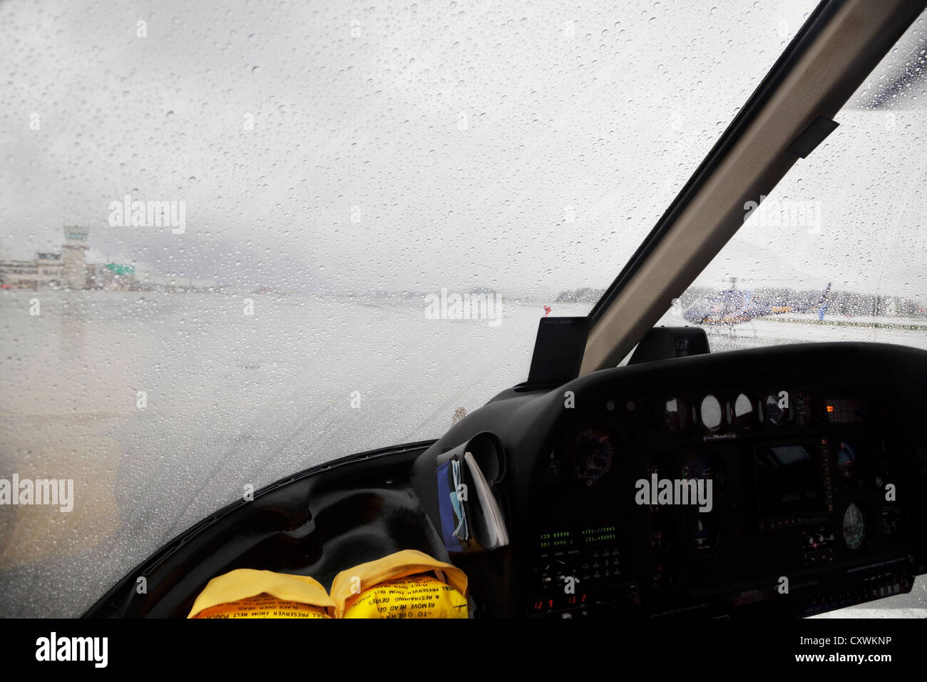 Helicopter cockpit preparing for rainy takeoff - Stock Image