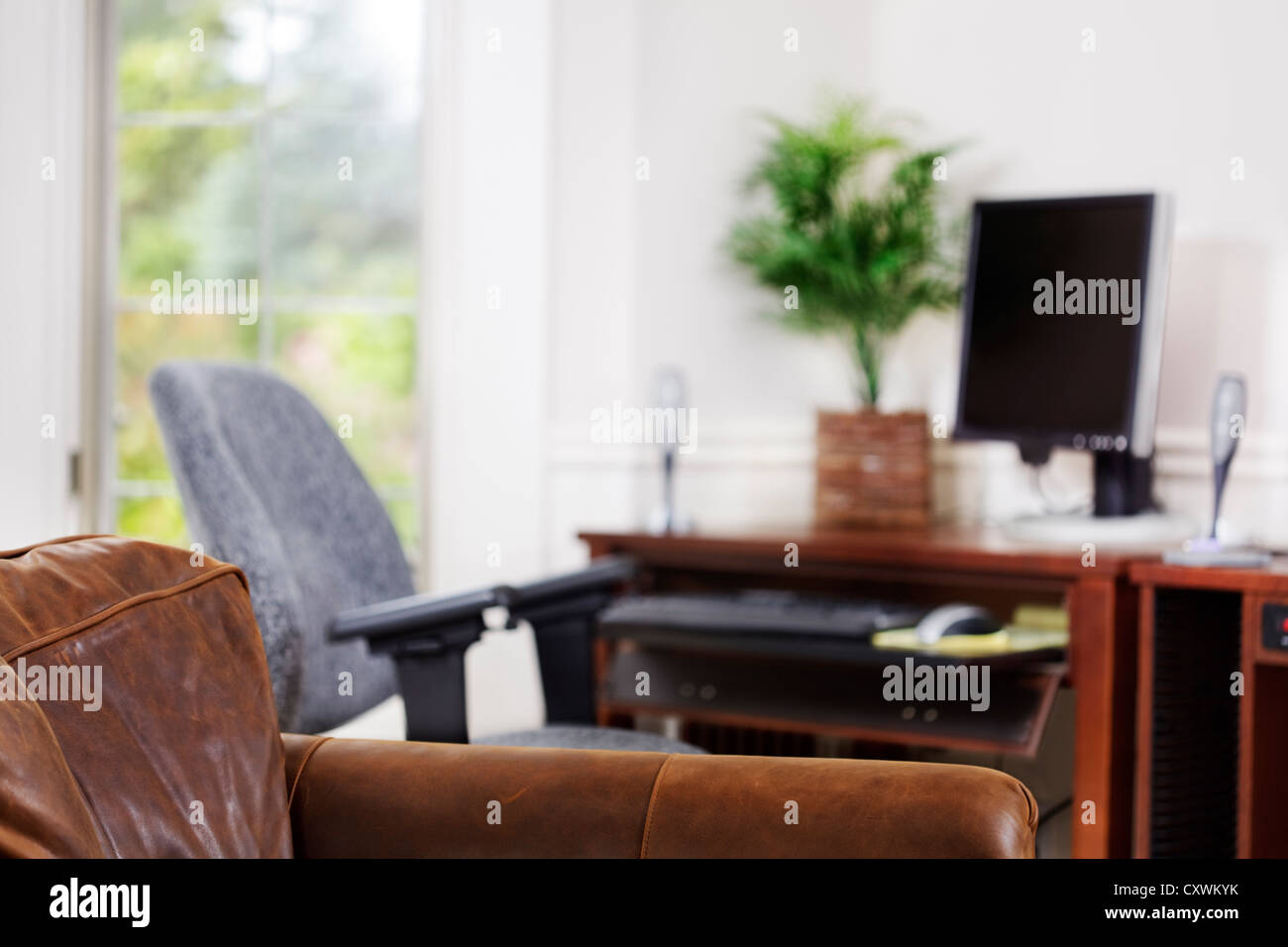 Comfy leather chair in a home office. Shallow depth of field. - Stock Image