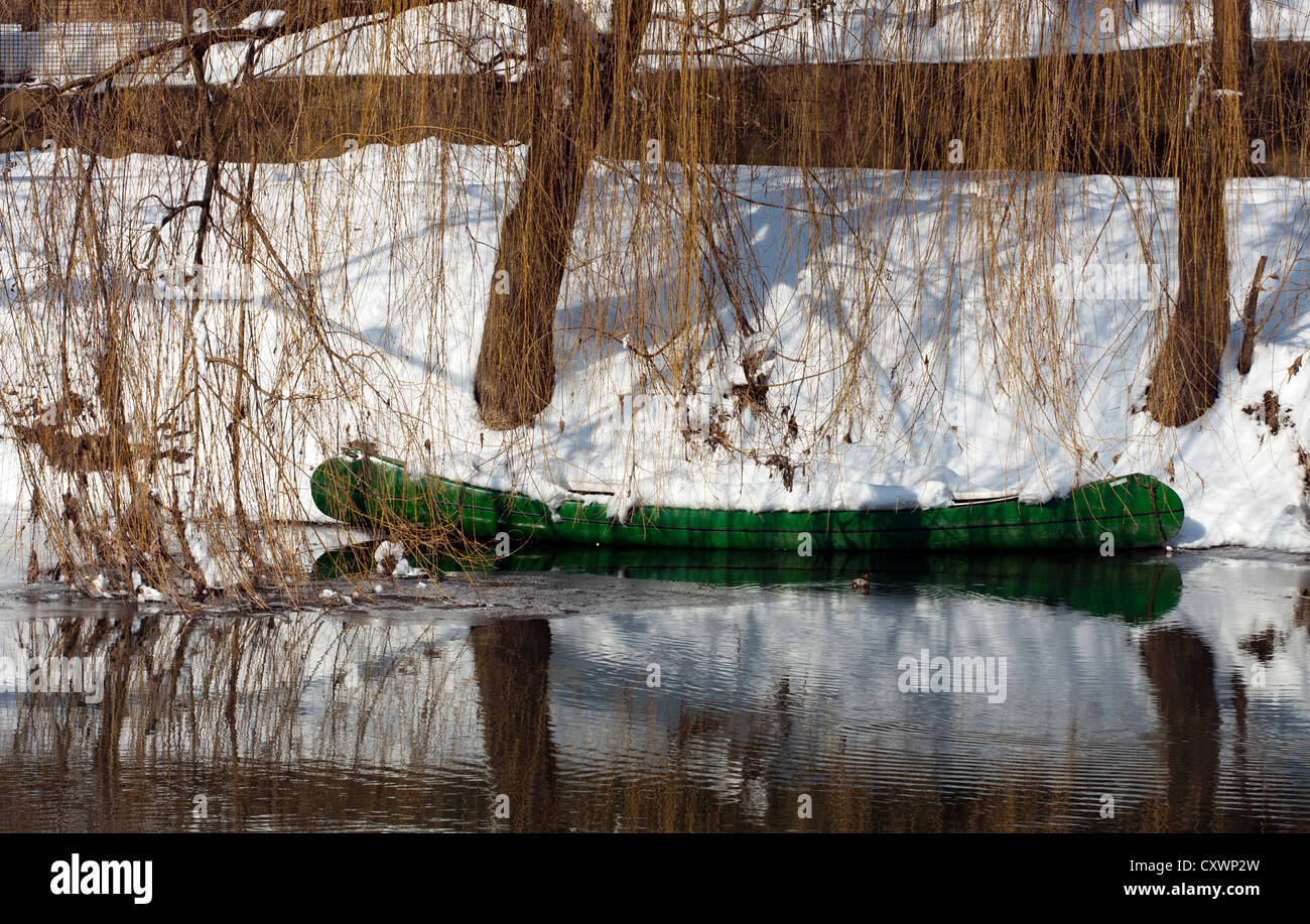 Canoe covered with snow by the winter riverbank. - Stock Image
