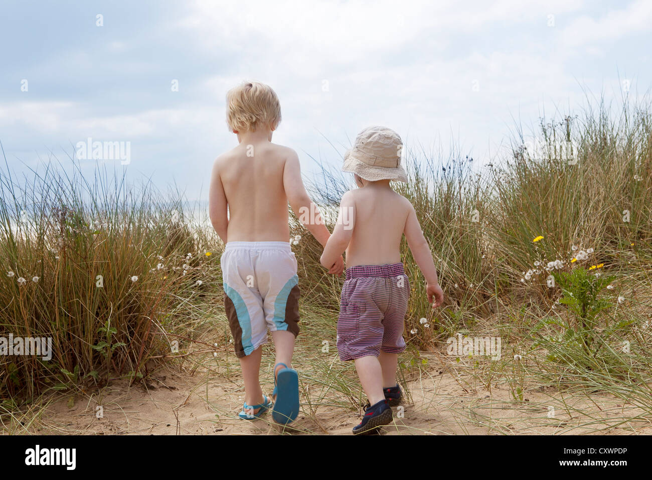 Boys holding hands in grassy sand - Stock Image