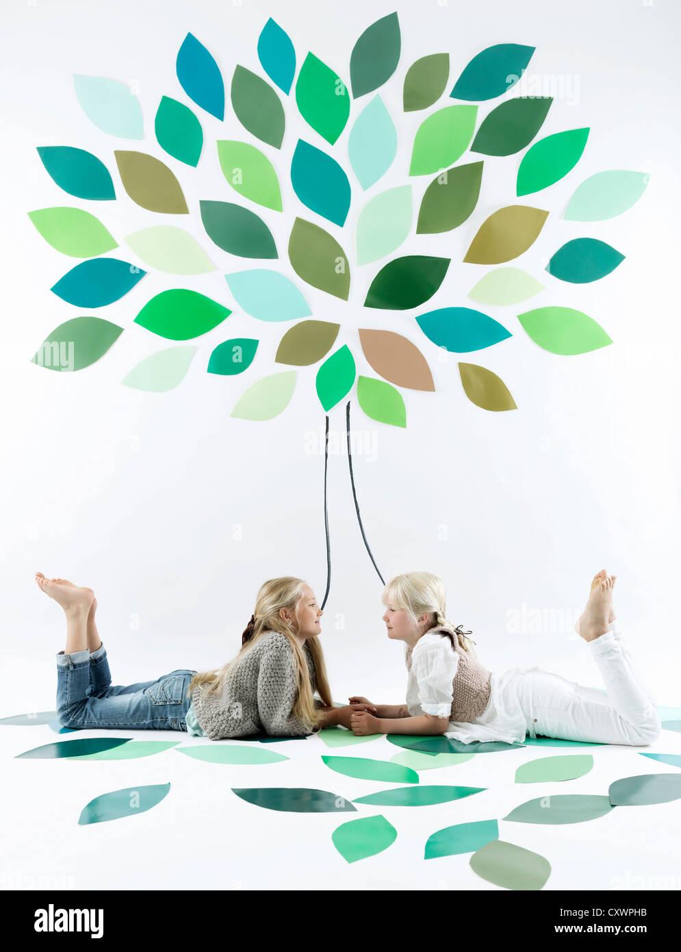 Girls talking under tree on wall - Stock Image