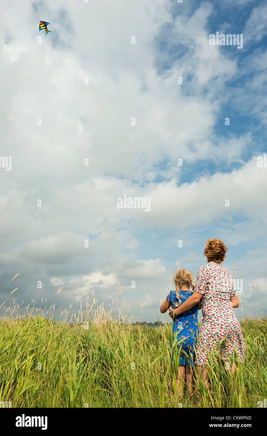 Mother and daughter flying kite in field - Stock Image