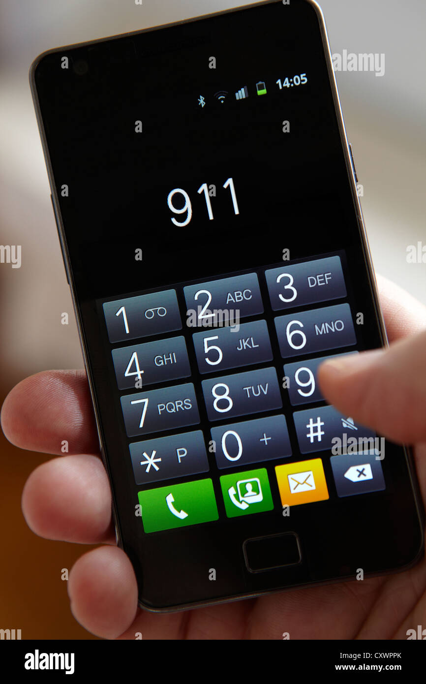 Close Up Of Hand Dialling 911 On Touchscreen Phone - Stock Image