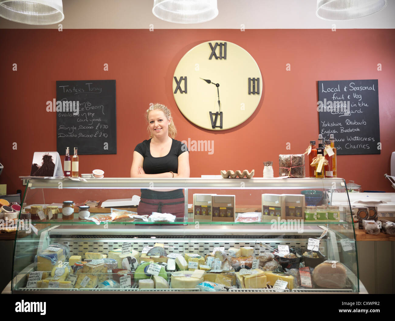 Grocer standing behind counter in shop - Stock Image