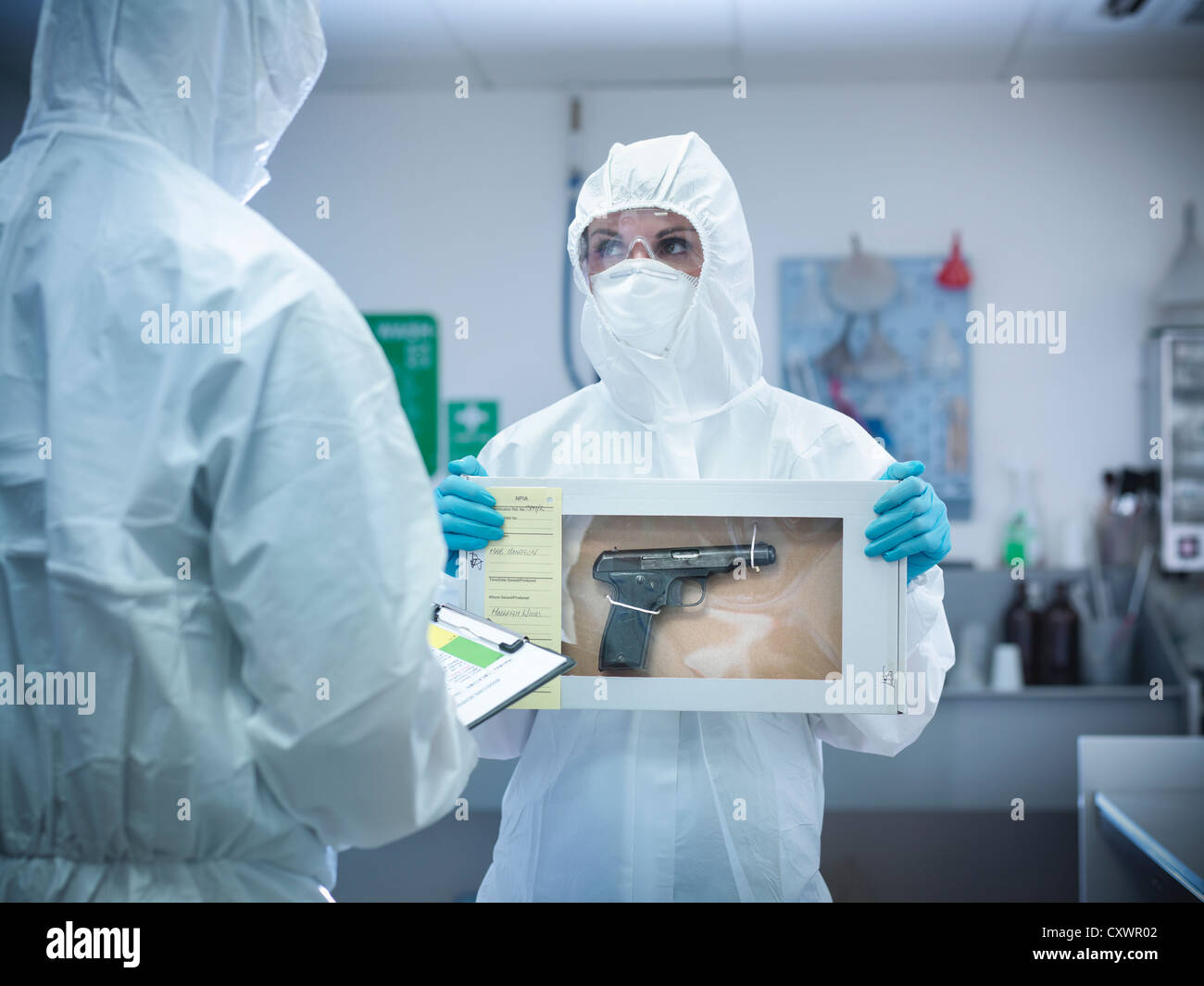 Forensic scientist with gun in box - Stock Image