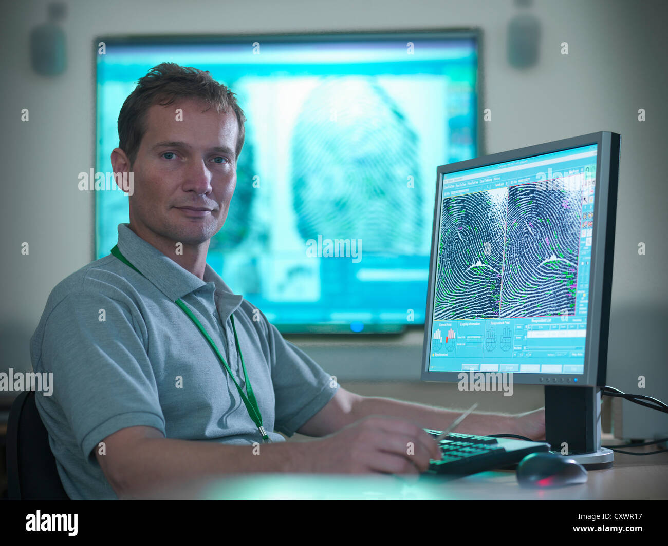 Forensic scientist at computer desk - Stock Image