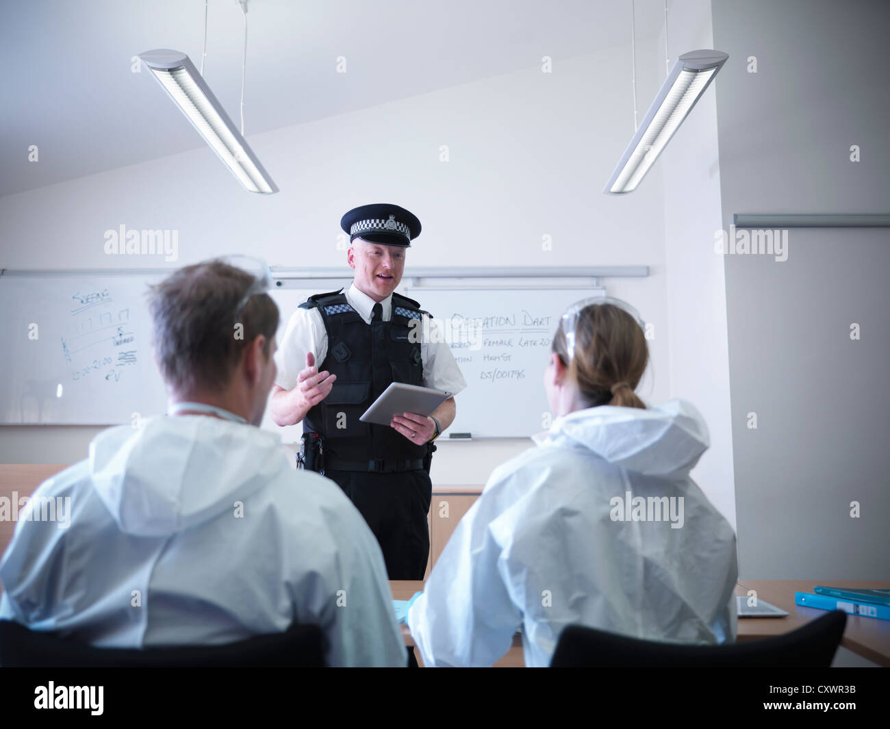 Policeman talking to forensic scientists - Stock Image