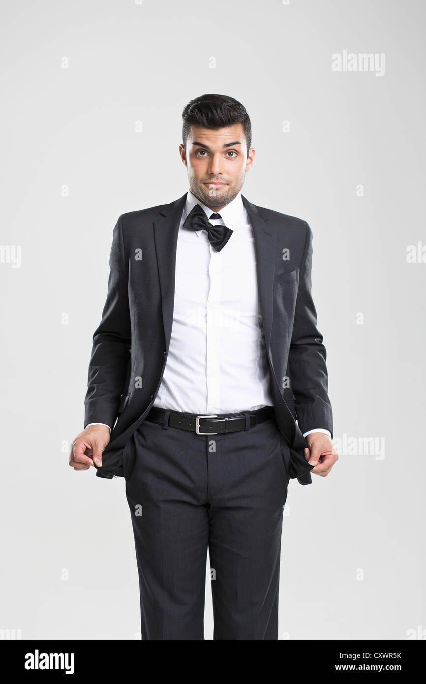 Man in tuxedo pulling at empty pockets - Stock Image