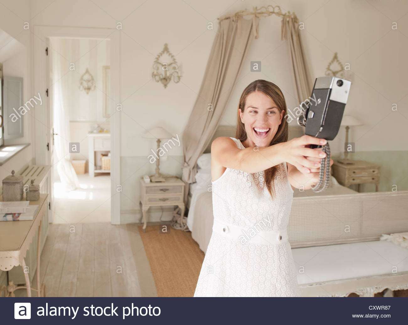 Woman using video camera in bedroom - Stock Image